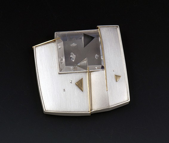 "Eleanor Moty Negative Crystal Brooch 2 1/8"" x 2 1/8"" x 5/16""		 Sterling silver, 18K gold, negative quartz crystal  Tom Munsteiner, lapidary artist, Idar Oberstein, Germany"