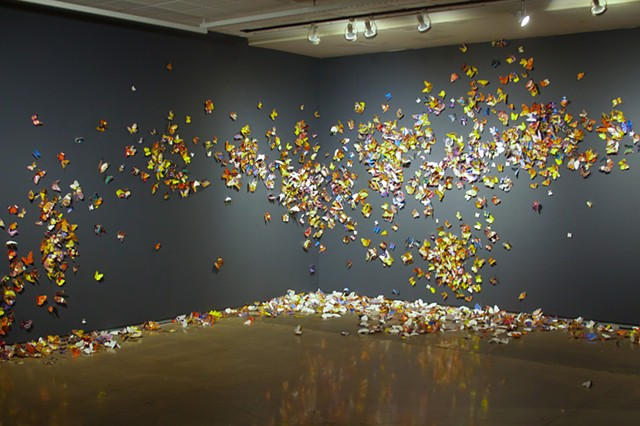 "6,000 CMYK Butterflies attached to the wall with coda. During the corse of the instillation butterflies would slowly fall off the wall and ""die"" acumulating on the floor."