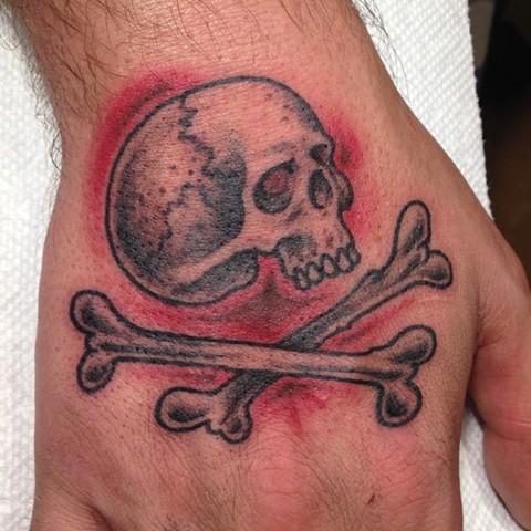 Jolly Roger hand tattoo. Skull and crossbones. Provincetown tattoo, Cape Cod tattoo, Ptown tattoo, truro tattoo, wellfleet tattoo, custom tattoo, coastline tattoo
