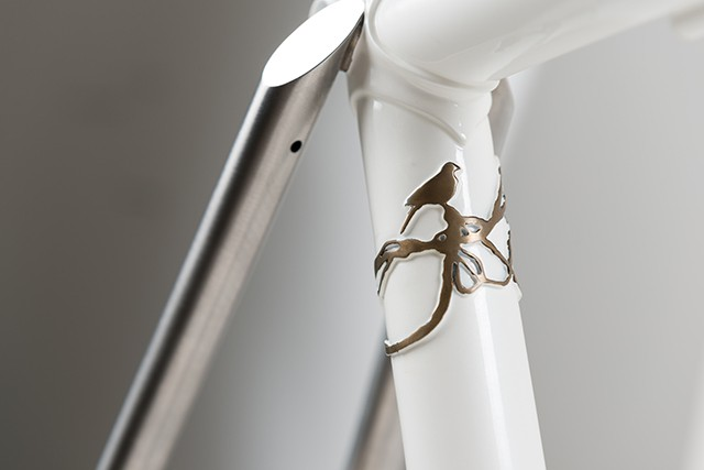 Brass detail of a bird on a vine that wraps around the seat tube, and another look at the polished side tack facet on the brushed seat stays