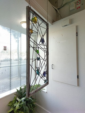 Deconstructed stained glass sculpture by Metal Muse Studios. Can be mounted as unique, colorful window guard. Can be hung or mounted vertically or horizontally.