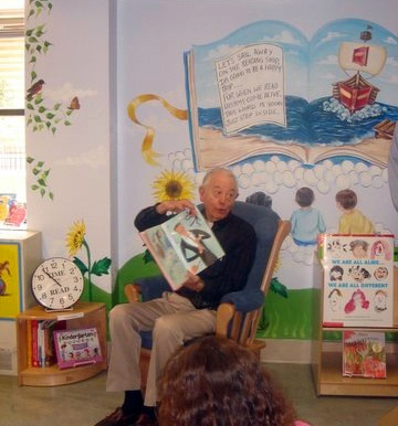 children's book author Lloyd Moss reading at the opening ceremony