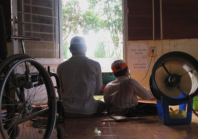 Two young men work at a lathe at a workshop in a rural training facility for victims of Dioxin.