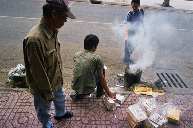 During Tet, burning fake money and shoving the ashes into the public drains for ancestors is a common occurrence in downtown Saigon.