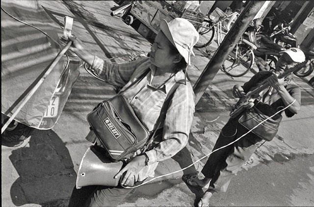 The blind leads the blind:  A musician and his assistant sell lottery tickets in the street, downtown Saigon.