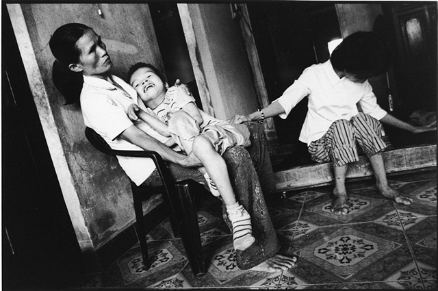 A mother coddles her son, afflicted with Spina Bifida, while his blind sister sits close by.  The children's father fought in Cambodia just after the American conflict.