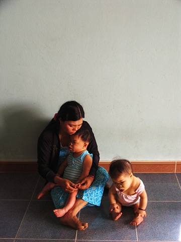 A woman and her two children in their home outside of Danang.  The girl on the floor is nine years old, her brother, in his mother's lap, is ten.