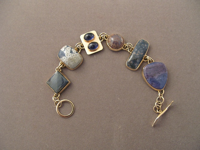 14kt gold, stones:  petersite, Leland blue, iolite, fossil coral, flower obsidian, sugelite in ricterite