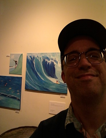 Artist Christopher Stanton with his acrylic surfer paintings at The Five Elements