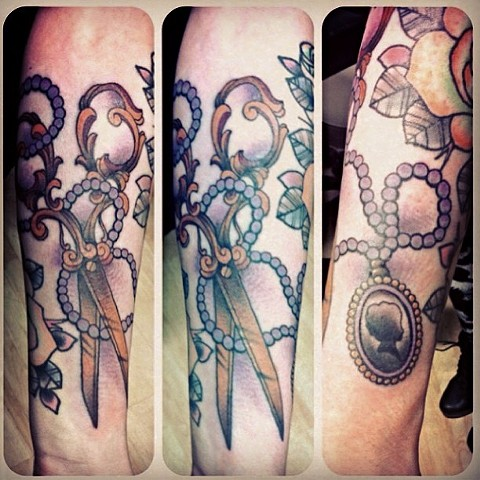 Scissors and pendant on arm by Sydney Dyer