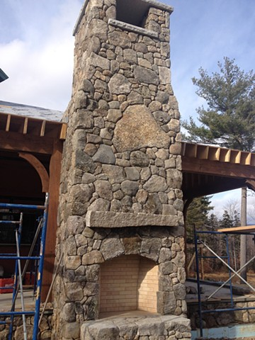 Outside fireplace finished with stone gathered from property.