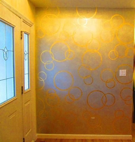 Gold leaf circle motif over silver on foyer wall.
