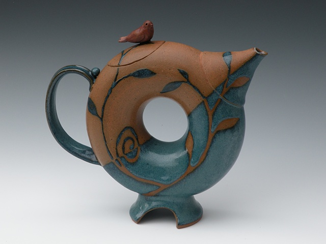 Donut shape teapot with turqoise glaze and bird on lid