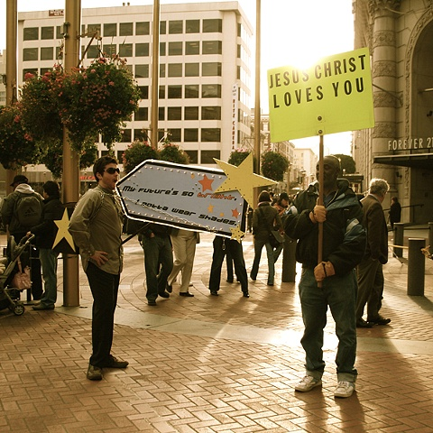 """Photograph from performance standing with """"Jesus Christ Loves You"""" sign guy."""