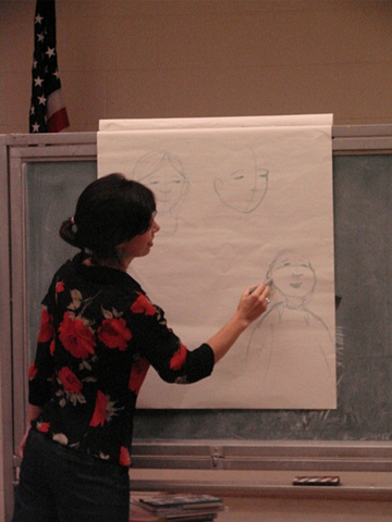 Rene demonstrating how to draw a character from the book Papi's Gift