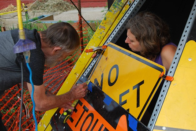Volunteers attaching street signs to the roof structure