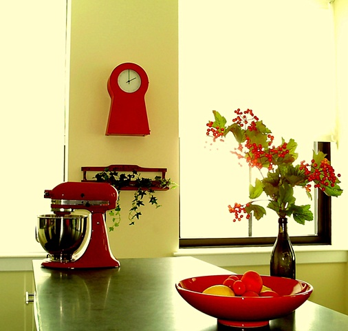 Colorful red accents on kitchen island and yellow wall by Jane Interiors NYC
