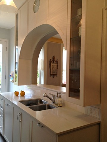 An archway cut into the kitchen wall opens up the dining room by Jane Interiors NYC, kitchen with bar counter, kitchen with open wall, small kitchen design