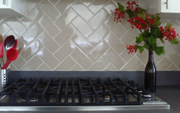 Herringbone pattern tile back splash in galley kitchen by Jane Interiors NYC
