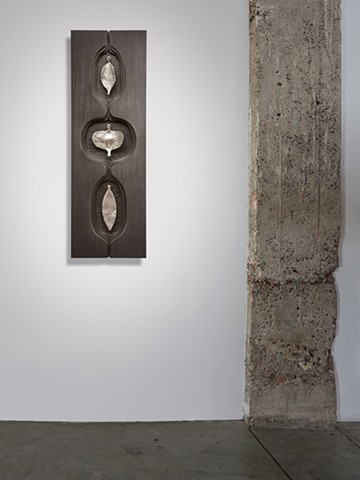 wall sculpture comprised of cast aluminum, wood, graphite, and sewing needles by Mary Meyer