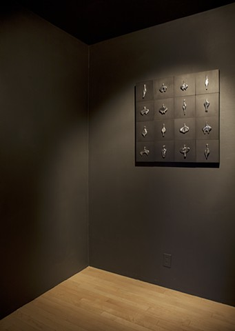 wall installation comprised of cast aluminum, wood, graphite, and sewing needles by Mary Meyer