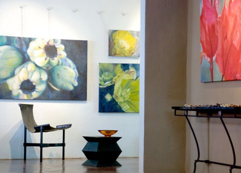 Back room of gallery with small sling chair, square metal table and paintings of cactus and cactus flowers