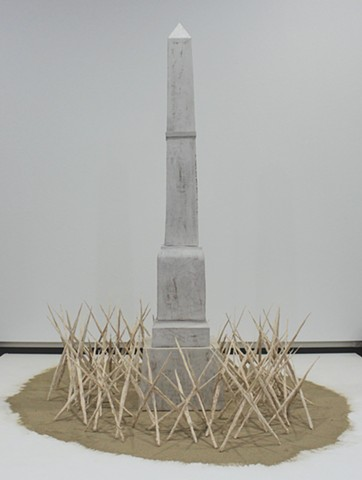 Stylized monument based on local Confederate memorial, surrounded by grasses dipped in porcelain, burned away, and assembled into caltrops, resting on a bed of ashes.
