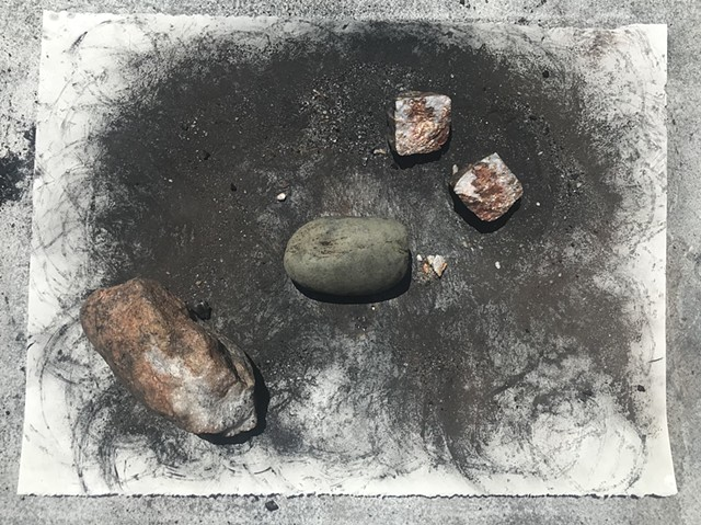 "performative process from ""Witness 4""  April 2020  performative drawing with rocks, tea, and charcoal"