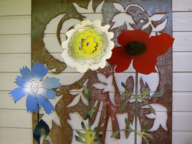 3 steel garden flowers against the backdrop of a steel screen