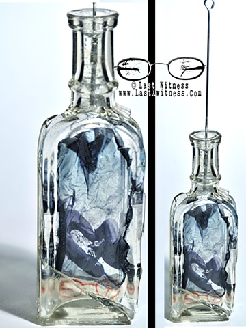 photo emulsion suspended in resin casted inside vintage medicine bottle with tattoo needle hanger