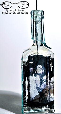 photo emulision suspended in resin casted inside vintage medicine bottle with tattoo needle hanger