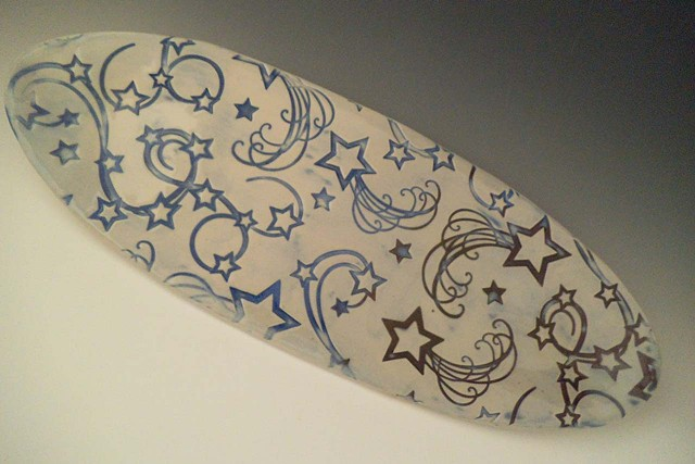 Oval tray wth stars design impressed into the clay, glazed in blues and purples on a white background.