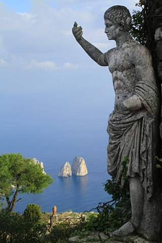 Statue and Faraglioni rocks