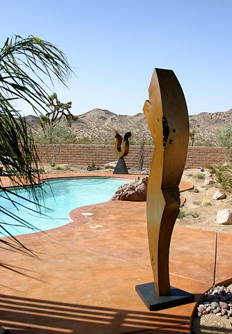 Large outdoor figurative bronze sculpture with golden patina.
