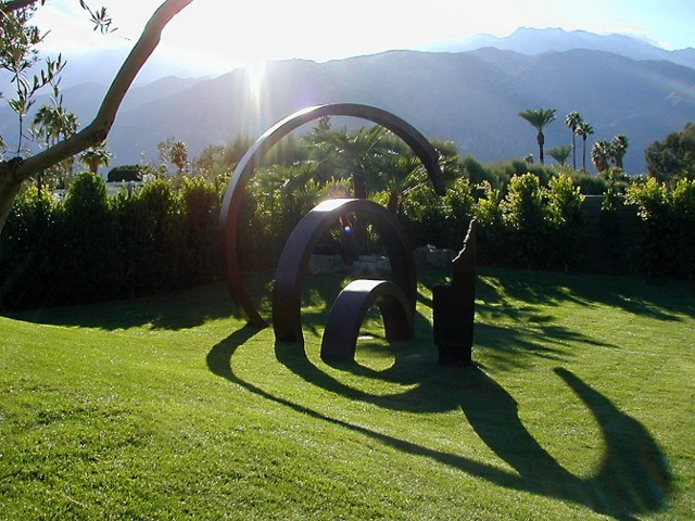 Large outdoor patinated steel sculpture that moves in and out of the ground in ever-increasing rings.