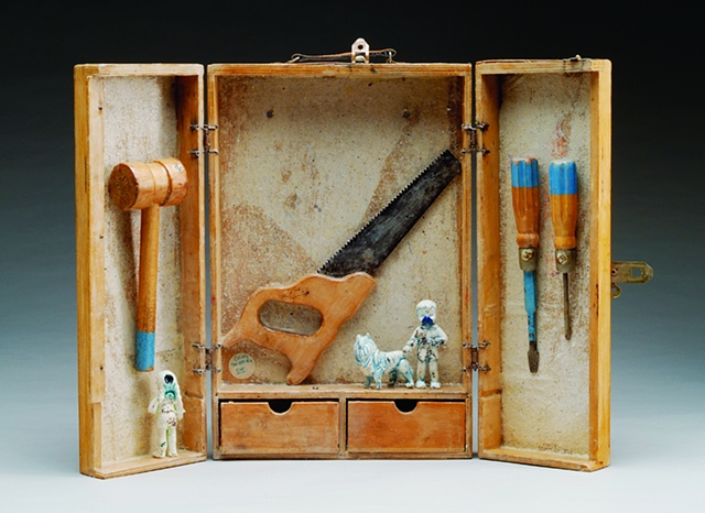 porcelain figures with glass inclusions, stain and glaze; handmade mica paper; vintage child's toolbox and tools, encaustic