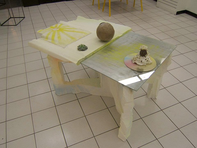 sculptural painting and table with mirrors and plant