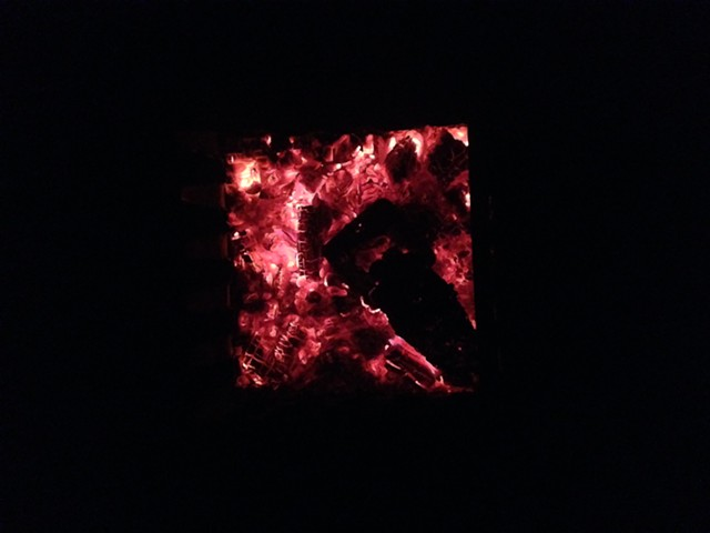 The tins of wood (now charcoal) are left in the coals of the fire, and then to cool overnight.