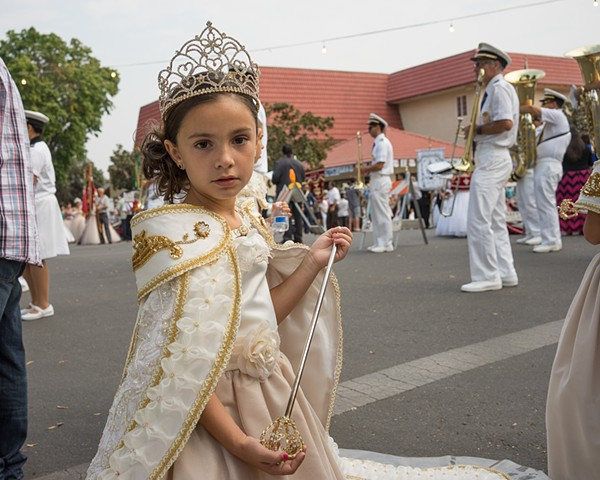 Dozens of Pentecostal queens and their courts wearing exquisite costumes, crowns, and ten foot trains, parade from the park on Sunday morning