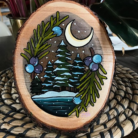 Winter nature scene with trees and snow surrounded by juniper berries in a tattoo style on wood