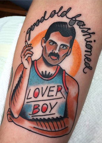 Traditional arm tattoo of Freddy Mercury in bold colour, portrait, made in Toronto