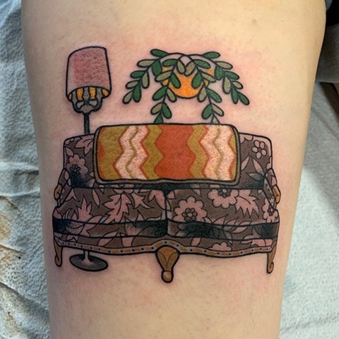Couch or sofa furniture tattoo in a simple traditional tattoo style with 1970s touches made in subtle colours by Jenny Boulger in Halifax Nova Scotia