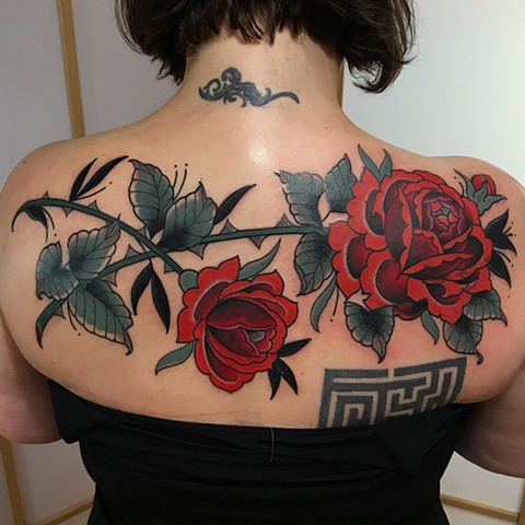 Red rose cover up traditional tattoo in a bold style on a woman's back made in Toronto Ontario Canada