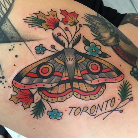 Muted colour moth tattoo with maple leaf made in traditional tattoo style in Toronto Ontario Canada