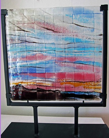 "Pink and Blue sky over Mountains in wrought iron metal stand  details: glass piece comes in wrought iron metal stand.  total size is 14"" tall x 11"" wide"