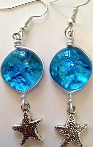 blue starfish earrings...  details: dichroic glass, wrapped in silver with a dangly silvery starfish...