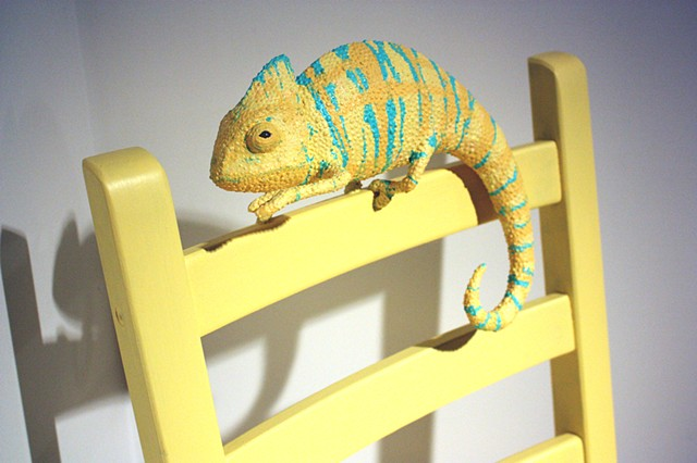 paper mache chameleon sculpture on a yellow chair by Bethany Krull
