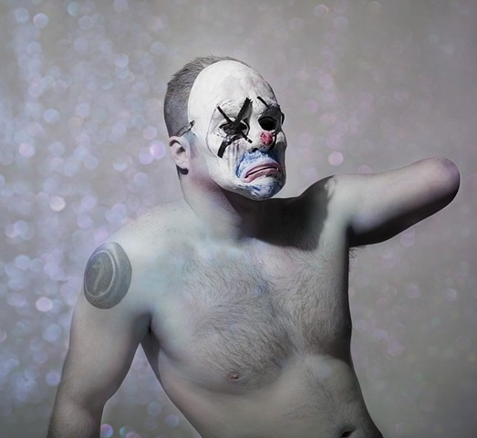 photograph of man with an amputated arm wearing a clown mask by christopher andres