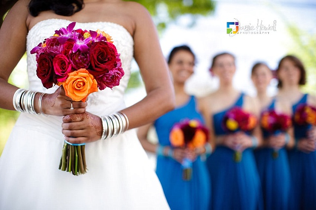 Colorful Bridal Bouquet composed of fuchsia dendrobium orchids, and red, orange, and hot pink roses and dahlias.  Jamie Howell Photography