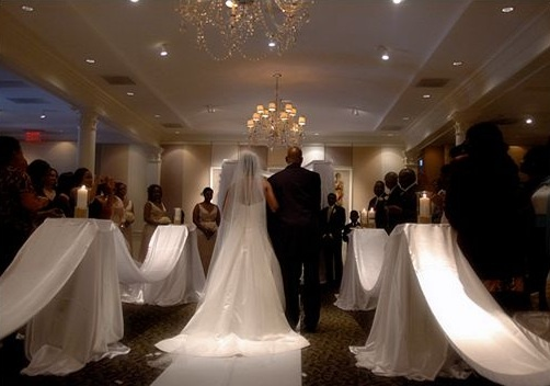 Daniel Menacher Photography Eight satin-draped square pedestals lining the aisle.